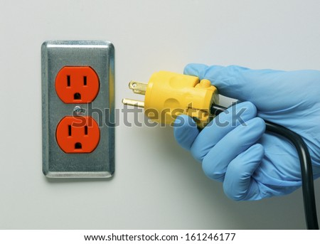 "Concept photo for ""Pulling the Plug"" on life support in hospital showing doctor's hand pulling the life support equipment plug from wall. - stock photo"
