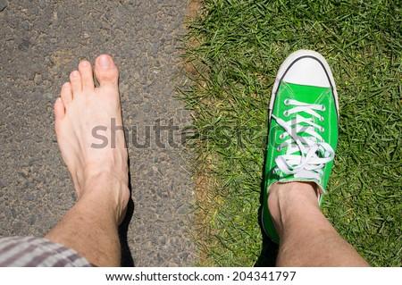 concept photo of barefoot versus wearing sneakers grass versus asphalt - stock photo