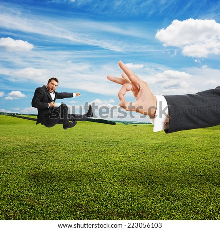 concept photo of conflict between subordinate and boss. angry young businessman kicking and flying at big flick of his boss. photo at outdoor - stock photo