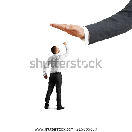 concept photo of conflict between subordinate and boss. screaming young businessman showing fist and looking up at big palm of his boss. isolated on white background - stock photo