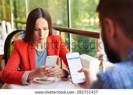 concept photo of smartphone addiction. young woman and man sitting in cafe with smartphone and do not looking at each other - stock photo