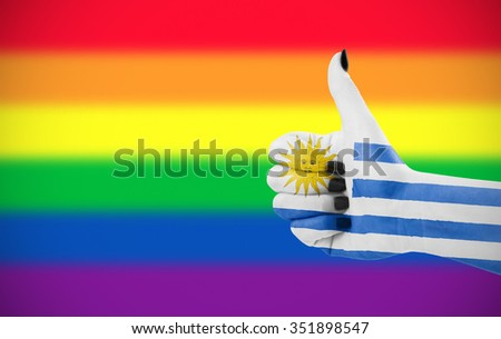 Concept photo - Positive attitude of Uruguay for LGBT community. Hand against rainbow flag. Focus set on hand. - stock photo