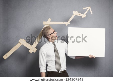 Concept: Positive business outlook. Happy confident businessman looking at empty panel in front of business graph with upward trend, isolated on grey background. - stock photo