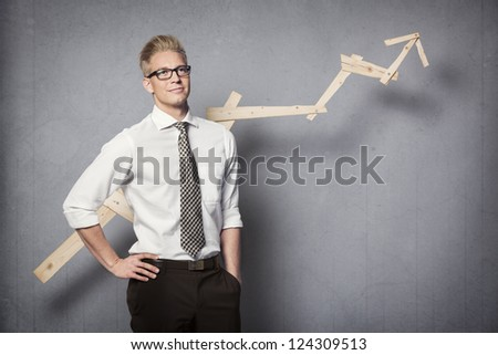 Concept: Positive business outlook. Smiling confident businessman with business vision in front of business graph with positve trend, isolated on grey background. - stock photo