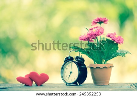 Concept red heart with bouquet of flower and alarm clock on table in garden with bokeh green leaf background. Retro filter. Valentines Day background. - stock photo