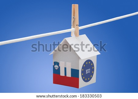 concept - Slovenia, Slovenian and EU  flag painted on a paper house hanging on a rope - stock photo