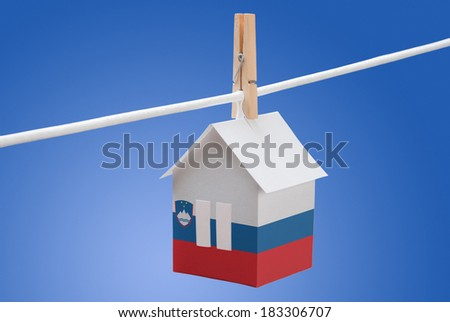 concept - Slovenia, Slovenian flag painted on a paper house hanging on a rope - stock photo