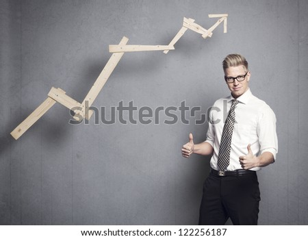Concept: Successful business. Confident young businessman holding thumbs up in front of positive business graph, isolated on grey background. - stock photo