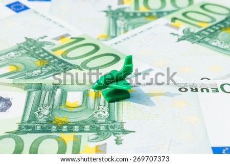 Concept travel, vacation, holiday, salary, savings, transport on hundred euro banknotes. Focus on green airplane, jet. - stock photo