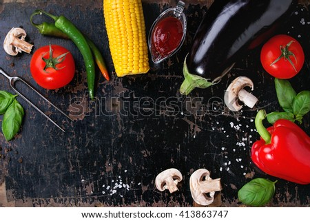 Concept veggie BBQ background with assortment of raw vegetables, herbs, barbecue sauce, salt and meat fork over old black wooden surface. Top view. With space for text. - stock photo