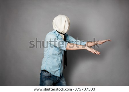 concept with a young man with face covered by a textile material, on grey - stock photo
