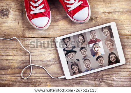 Concept with red sneakers and tablet with white headphones laid on wooden floor background. - stock photo