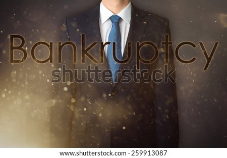 Conception of the business presented against the war background as the symbol of the continuous fight in the business. Businessman standing in dust - in the foreground is big inscription - Bankruptcy - stock photo