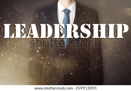Conception of the business presented against the war background as the symbol of the continuous fight in the business. Businessman standing in dust - in the foreground is big inscription - Leadership - stock photo