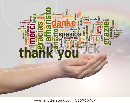 Conceptual abstract thank you word cloud held in hands different language, multilingual for education, thanksgiving day,  appreciation, multicultural, friendship, tourism travel over rainbow sky - stock photo