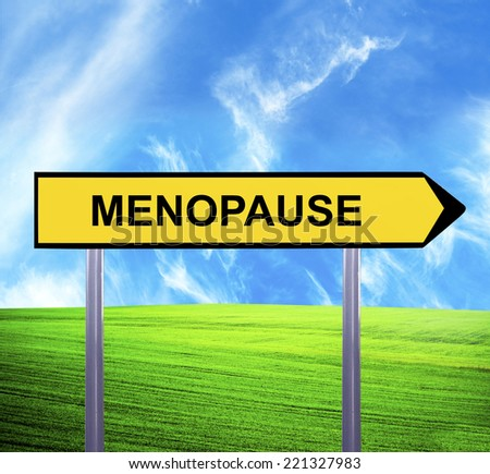 Conceptual arrow sign against beautiful landscape with text - MENOPAUSE - stock photo