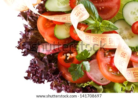 Conceptual assorted salad and tape measurement, close up - stock photo