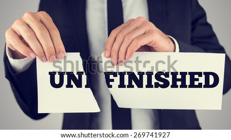 Conceptual Businessman Tearing a Small White Paper with Unfinished Word, Captured in Close up with Gray Background, Retro Effect Faded Look. - stock photo