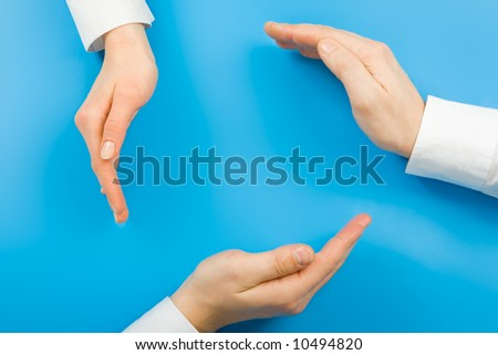Conceptual circle made from human hands on a blue background - stock photo