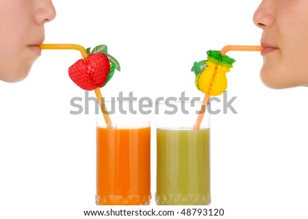 Conceptual close-up of girls drinking colorful tropical cocktails through straws isolated on white background - stock photo