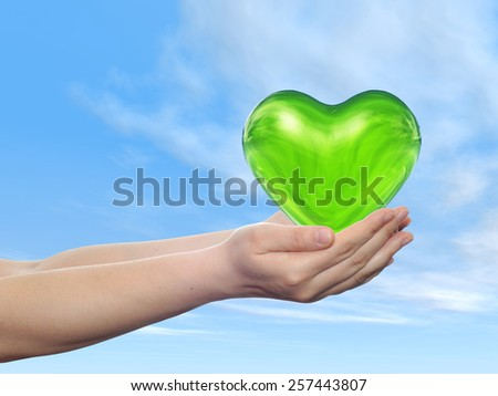 Conceptual 3D green abstract heart sign or symbol held in hands by woman or child over nice blue cloud sky background, metaphor to love, holiday, wedding, care, valentine, protection romantic - stock photo