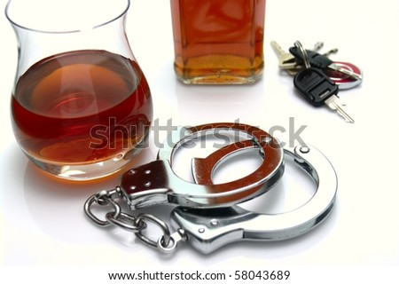 Conceptual 'driving under the influence of alcohol' shot. High key scene of  handcuffs, alcoholic drinks and car keys - stock photo
