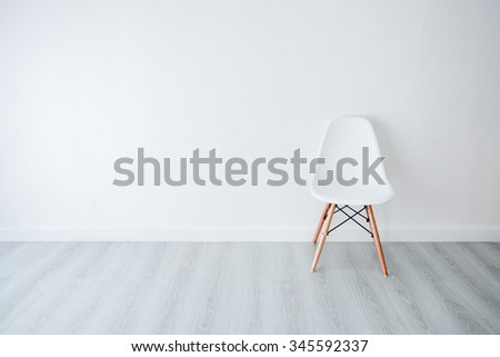Conceptual Empty White Wooden Leg Chairs with white wall and gray wooden floor and copyspace - stock photo