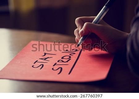 Conceptual Handwritten Stay Strong Phrase on red Sticky Note on Top of Wooden Table, Captured in Close up. - stock photo