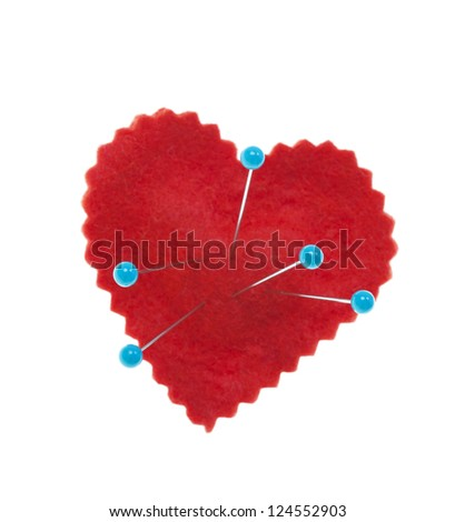 Conceptual heart with pins stuck in it, representing heart pain, heart break, or voodoo.  Shot on white background. - stock photo