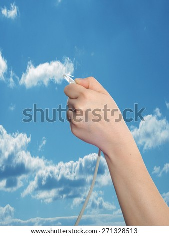 Conceptual human or man hand holding a internet or data cable in clouds over the blue sky background - stock photo