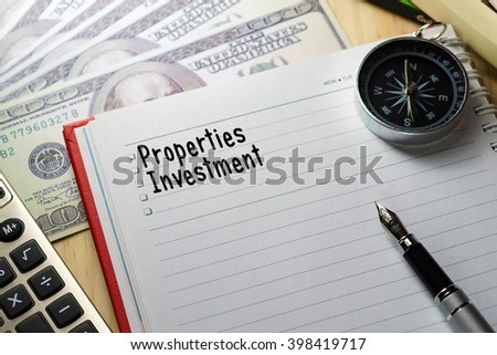 Conceptual image.Calculator, hundred dollar bills, pen, notebook and compass on wooden table with PROPERTIES INVESTMENT words. - stock photo
