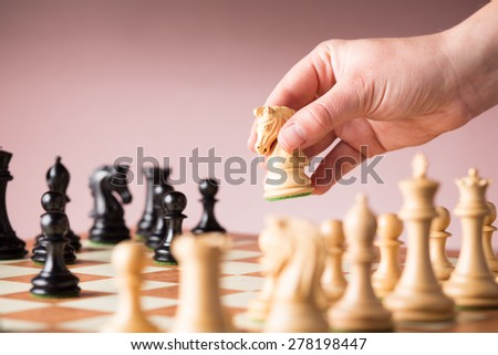 Conceptual image depicting making a strategic move with a hand moving a chess piece on a chessboard during a game - stock photo