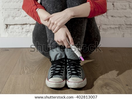 conceptual image hand of pregnant teenager girl or young desperate woman holding positive pink pregnancy test sitting on home floor in unwanted baby and unexpected motherhood concept - stock photo