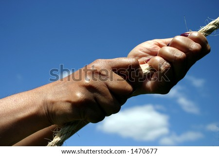 Conceptual image - hands pulling on a rope, blue sky background.  Might signify strength, pulling power, determination, teamwork etc. - stock photo