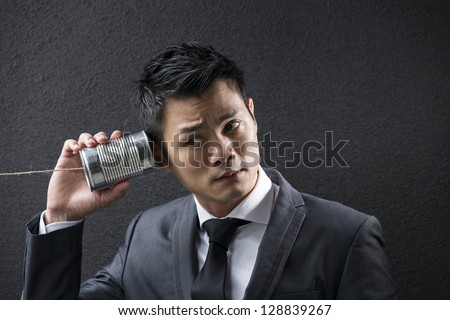 Conceptual image is about communication. Chinese Business man Listening to a Tin Can Phone. Asian Business man with Tin Can Phone. Concept about communication. - stock photo
