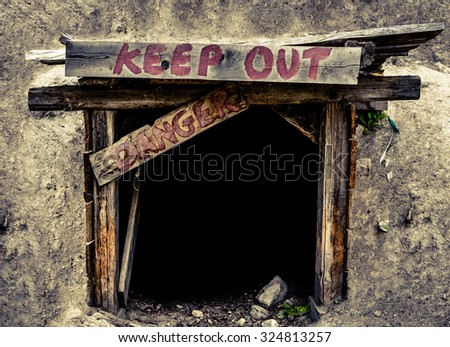 Conceptual Image Of A An Entrance To An Old Mine Tunnel With Keep Out And Danger Signs - stock photo