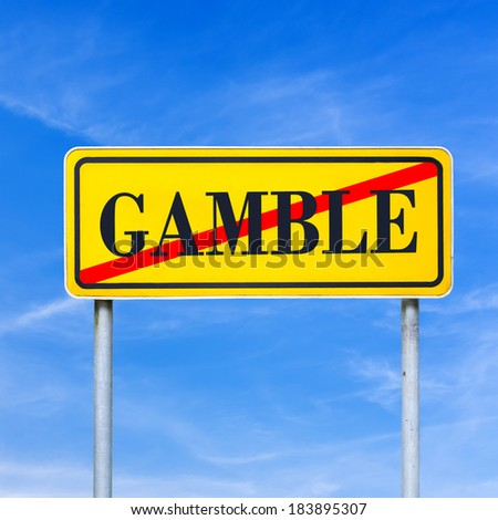 Conceptual image of a bright yellow traffic sign showing Gamble forbidden with the word - Gamble - crossed through against a clear blue sky. - stock photo