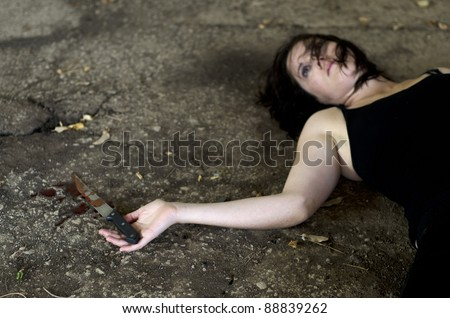 Conceptual image of a dead woman victim holding a sharp knife covered with blood. - stock photo