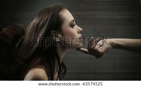 Conceptual image of a hand holding a woman's head - stock photo