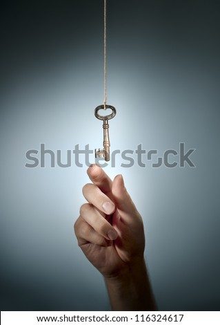 Conceptual image of a hand taking an old key hanging from a string. - stock photo