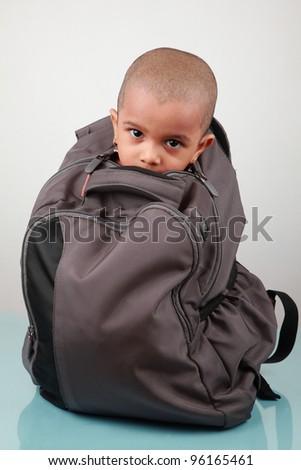 Conceptual image of a little kid sitting inside a knapsack bag - stock photo