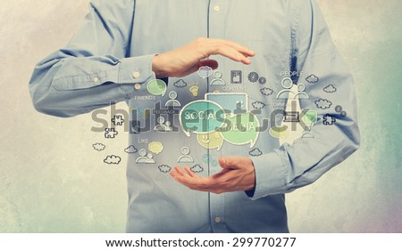 Conceptual image of a man cupping an assortment of social media icons between his hands depicting networking, community, chat, contacts, solutions and speech bubbles - stock photo