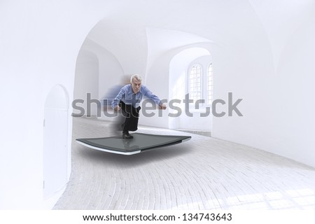 Conceptual image of a senior businessman balancing on the screen of a tablet surfing at high speed down the curving interior passage of a whitewashed modern building with motion blur - stock photo