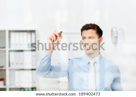 Conceptual image of a young businessman writing on a transparent virtual interface or screen with a marker pen with copyspace for your text or diagram - stock photo