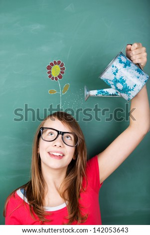 Conceptual image of an intelligent young schoolgirl wearing glasses making new ideas grow, by watering a flower drawing in a green chalkboard, with a gardening watering can - stock photo