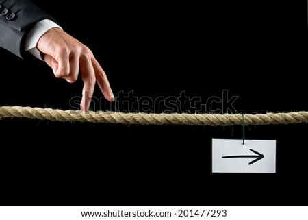 Conceptual image of business determination with a businessman walking his fingers along a length of rope towards a white card with right pointing arrow. - stock photo