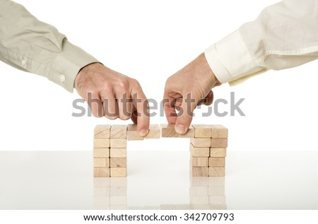 Conceptual image of business merger and cooperation - two male hands joining effort to build a bridge of wooden pegs on a white desk with reflection over white background. - stock photo