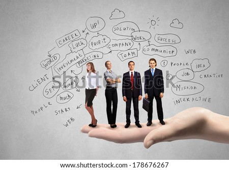 Conceptual image of business team on standing on palm - stock photo