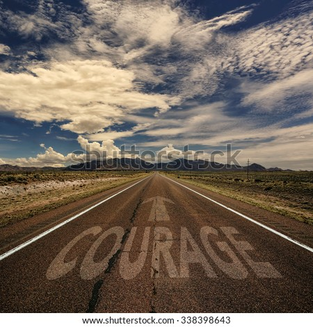 Conceptual image of desert road with the word courage and arrow - stock photo