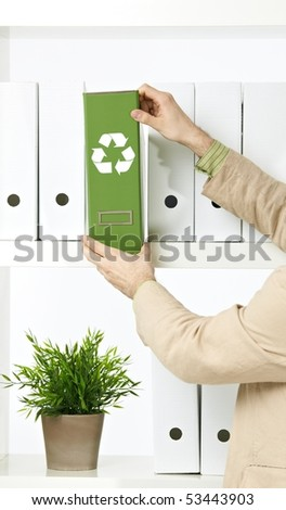 Conceptual image of environmental conservation, businessman holding green folder with recycling symbol. - stock photo